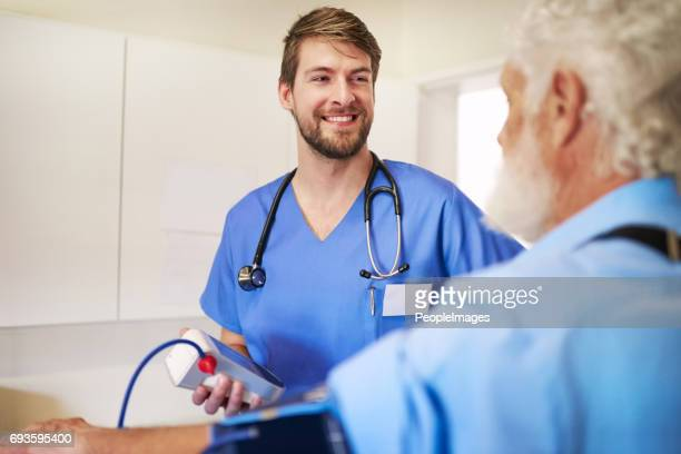 your blood pressure levels are looking great - male nurse stock pictures, royalty-free photos & images