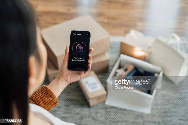 your order has been delivered - close up shot of hand holding smartphone with online shopping box stack at the background - returning merchandise stock pictures, royalty-free photos & images