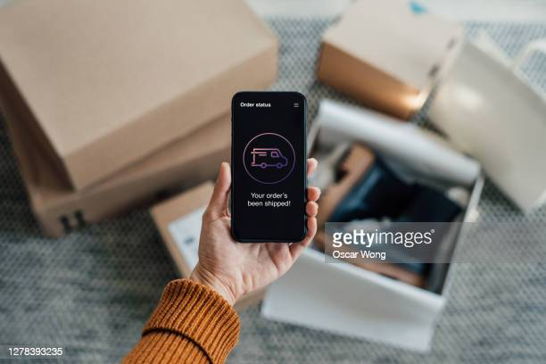 your order has been shipped - close up shot of hand holding smartphone with online shopping box stack at the background - buying stock pictures, royalty-free photos & images