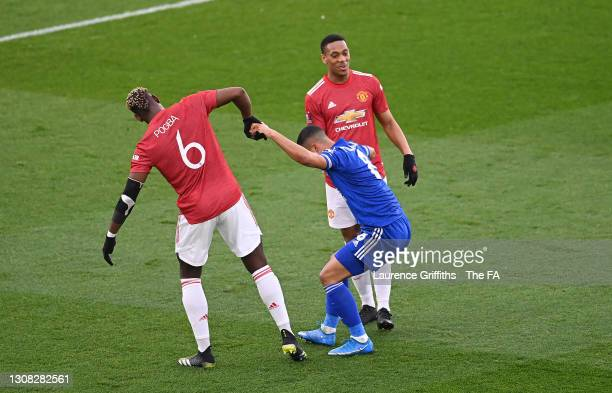 Youri Tielemans of Leicester City is helped up by Paul Pogba of Manchester United and Anthony Martial of Manchester United after a challenge during...