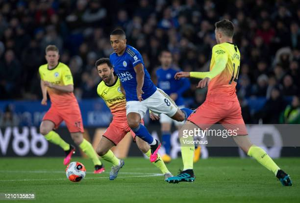 Youri Tielemans of Leicester City tries to find a way past Bernardo Silva and Rodrigo of Manchester City during the Premier League match between...