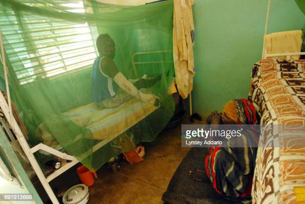 Yousef Hamiz a Sudanese rebel with the Justice and Equality Movement is watched over by his aunt as he lies burned in a hospital in Iriba Chad...