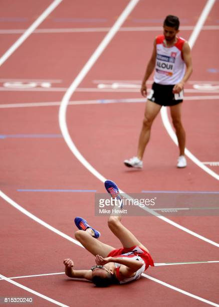 Youssef Benibrahim of Morocco collapses after crossing the line to win the Men's 5000m T13 Final ahead of Bilel Aloui of Tunisia during day three of...