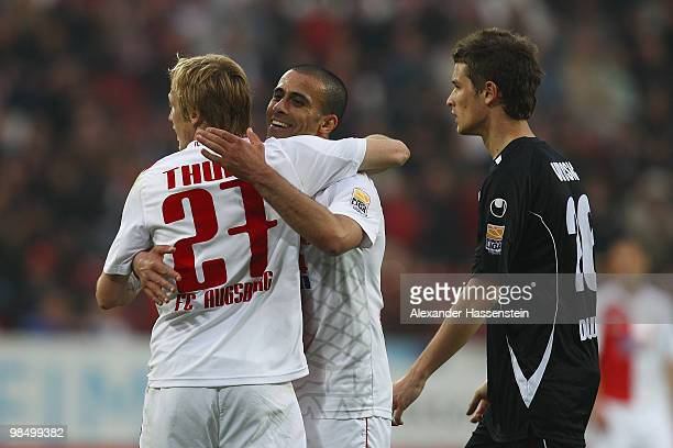 Youssef El Akchaoui of Augsburg celebrates with his team mate Michael Thurk whilst Dario Vidosic of Duisburg looks on during the Second Bundesliga...