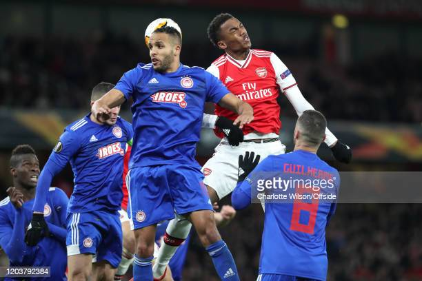 Youssef El Arabi of Olympiacos and Joe Willock of Arsenal go up for a header during the UEFA Europa League round of 32 second leg match between...
