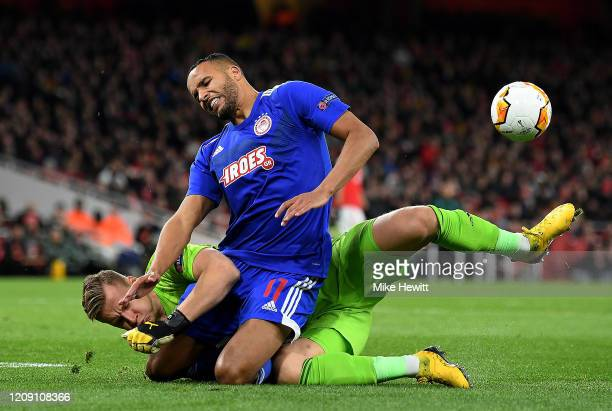 Youssef El Arabi of Olympiacos FC is tackled by Bernd Leno of Arsenal FC during the UEFA Europa League round of 32 second leg match between Arsenal...