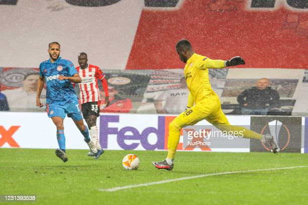 Youssef El-Arabi of Olympiacos, Jordan Teze and Yvon Mvogo goalkeeper of PSV during the UEFA Europa League Round of 32 match between PSV Eindhoven...