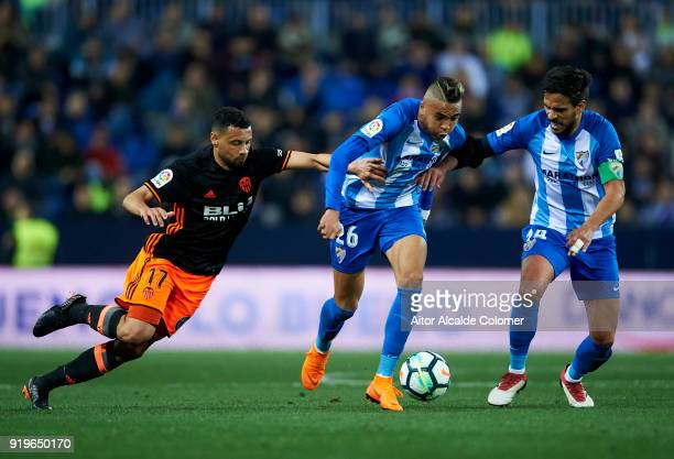 Youssef EnNesyri of Malaga duels for the ball with Francis Coquelin of of Valencia CF during the La Liga match between Malaga and Valencia at Estadio...