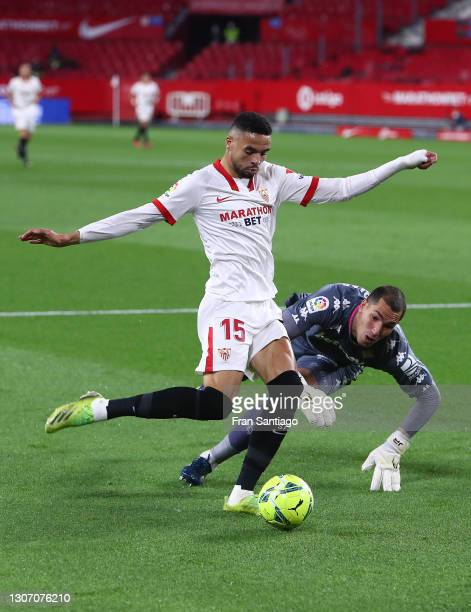 Yousseff En-Nesyri of Sevilla scores their side's first goal as he is challenged by Joel Robles of Real Betis during the La Liga Santander match...