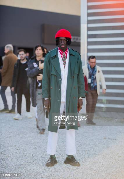 Youssou Bamar Gueye seen wearing red beanie green trench coat white suit during Pitti Uomo 97 at Fortezza Da Basso on January 08 2020 in Florence...