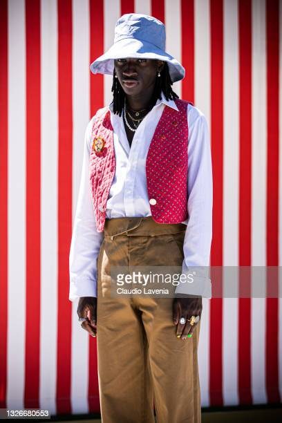 Youssou Bamar Gueye, wearing light blue cap, white shirt, brown pants and red vest, is seen at Fortezza Da Basso on July 01, 2021 in Florence, Italy.