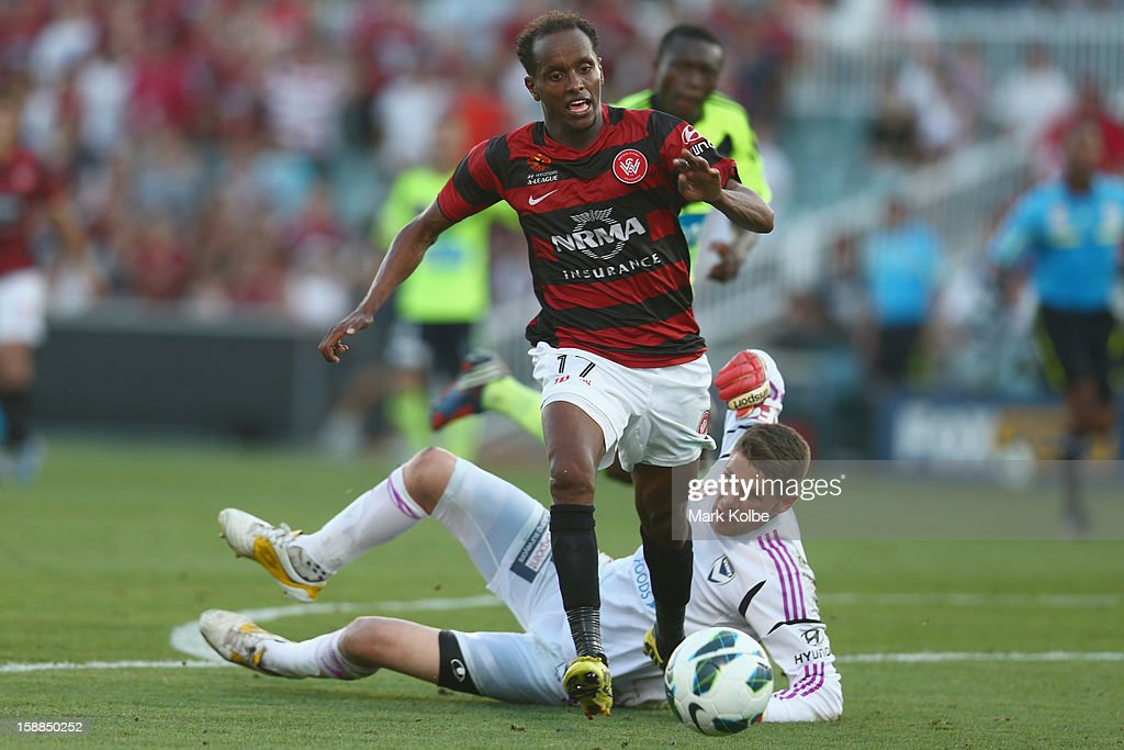 Youssouf Hersi of the Wanderers takes the ball past Nathan Coe of the Victory during the round 14 A-League match between the Western Sydney Wanderers and the Melbourne Victory at Parramatta Stadium on January 1, 2013 in Sydney, Australia.