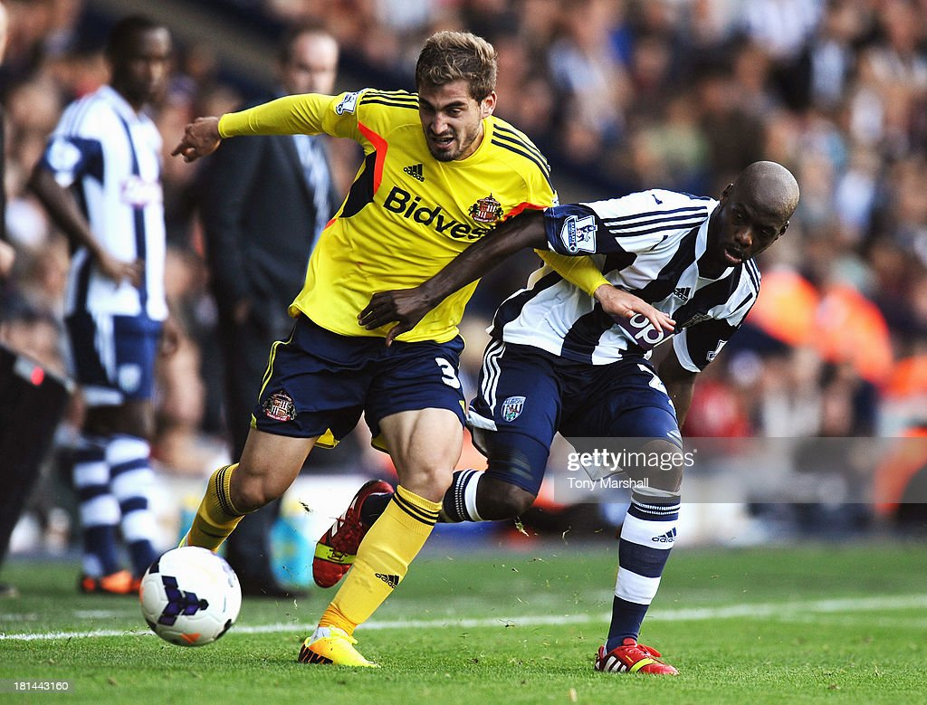 Youssouf Mulumbu of West Bromwich Albion tackles Charis Mavrias of Sunderland during the Barclays Premier League match between West Bromwich Albion and Sunderland at The Hawthorns on September 21, 2013 in West Bromwich, England.