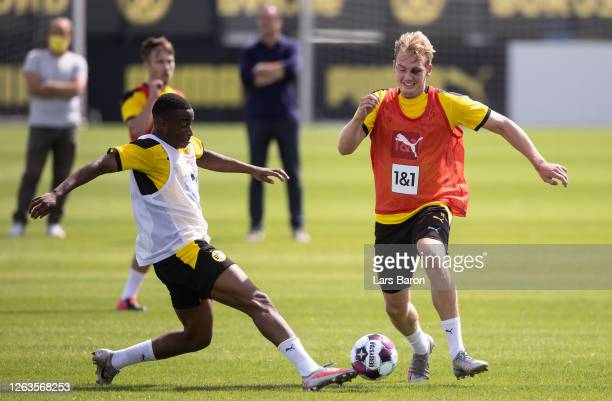 Youssoufa Moukoko challenges Julian Brandt during the first training session after the summer break on August 03, 2020 in Dortmund, Germany.