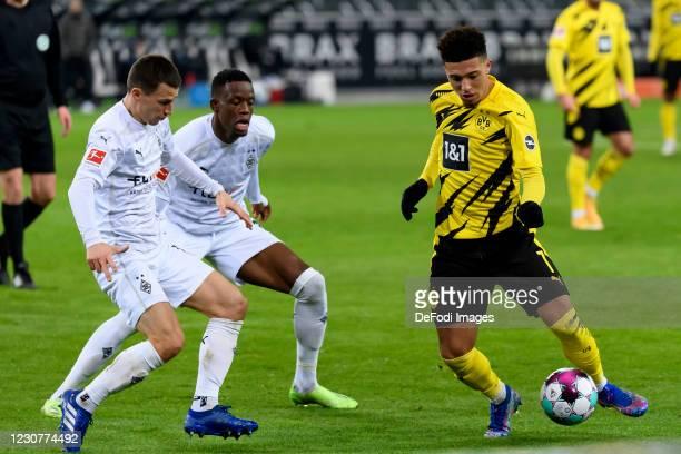 Youssoufa Moukoko of Borussia Dortmund, Denis Zakaria of Borussia Moenchengladbach and Jadon Sancho of Borussia Dortmund battle for the ball during...