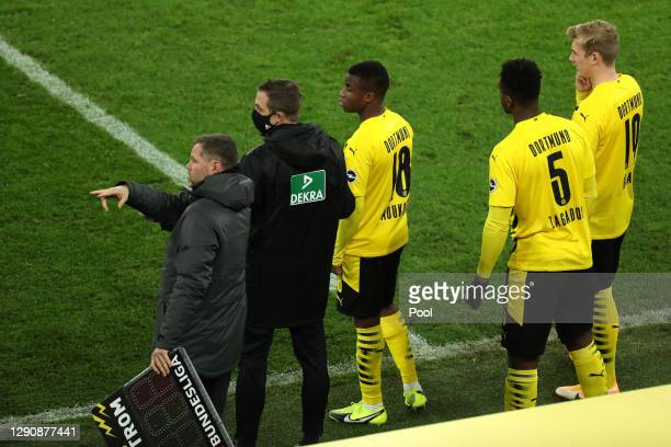 Youssoufa Moukoko of Borussia Dortmund gets ready to come onto the pitch along with teammates Dan-Axel Zagadou and Julian Brandt during the...