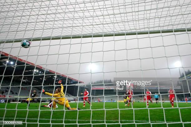 Youssoufa Moukoko of Borussia Dortmund scores his team's first goal past Florian Mueller of Sport-Club Freiburg during the Bundesliga match between...