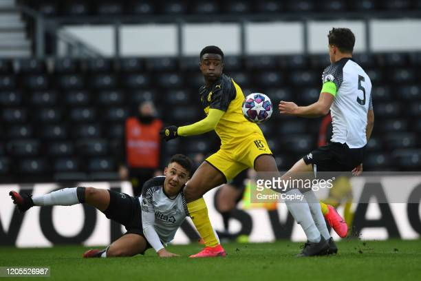 Youssoufa Moukoko of Borussia Dortmund U19 is challenged by Callum Minkley of Derby U19 and Lee Buchanan of Derby U19 during the UEFA Youth League...