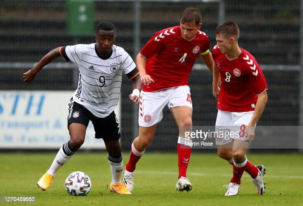 Youssoufa Moukoko of Germany challenge Mathias Ross Jensen and Morten Frendrup of Denmark during the international friendly match between Germany U20...