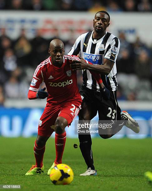 Youssuf Mulumbu of West Bromwich Albion competes with Shola Ameobi of Newcastle United during the Barclays Premier League match between Newcastle...