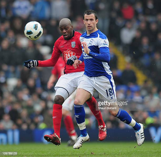 Youssuf Mulumbu of West Bromwich Albion is challenged by Keith Fahey of Birmingham City during the Barclays Premier League match between Birmingham...