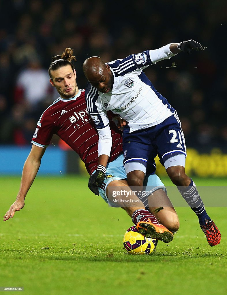 Youssuf Mulumbu of West Bromwich Albion is tackled by Andy Carroll of West Ham United during the Barclays Premier League match between West Bromwich Albion and West Ham United at The Hawthorns on December 2, 2014 in West Bromwich, England.