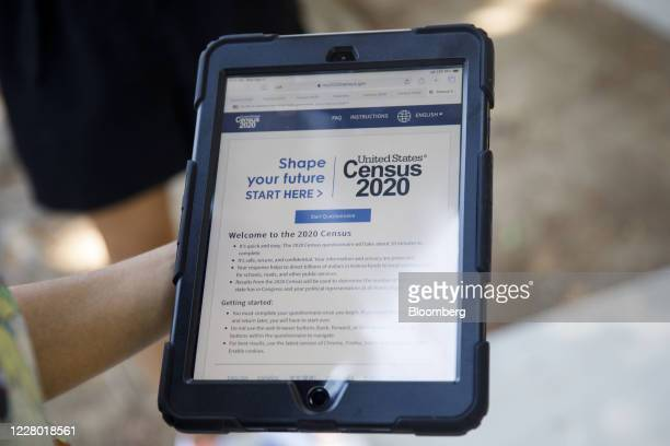 Youth ambassador holds a tablet with a Census 2020 interview questionnaire during a community food distribution at a YMCA location in Los Angeles,...