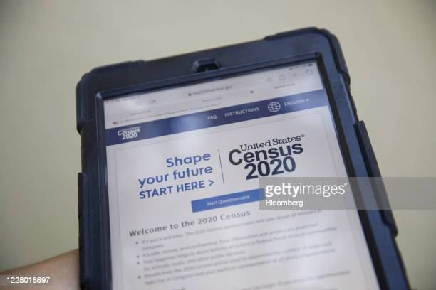 A YMCA youth ambassador holds a tablet with a Census 2020 interview questionnaire during a community food distribution at a YMCA location in Los...
