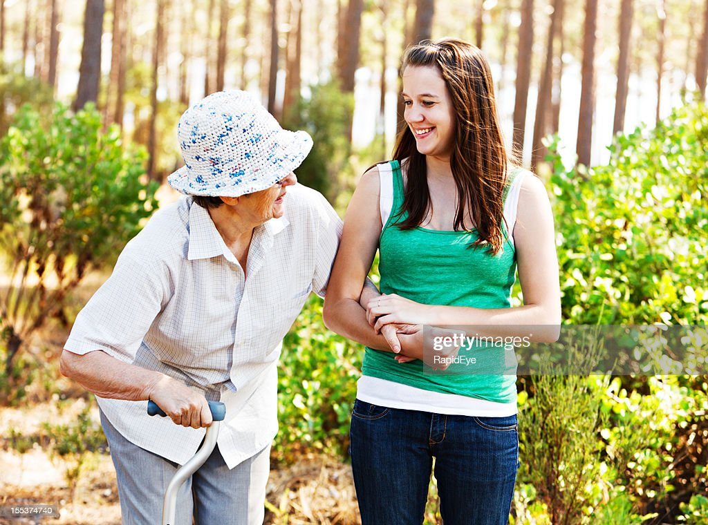 Youth and age: grandddaughter laughing with grandmother on forest walk : Stock Photo
