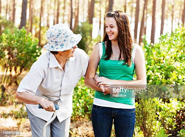 youth and age: grandddaughter laughing with grandmother on forest walk - osteoporosis stock photos and pictures