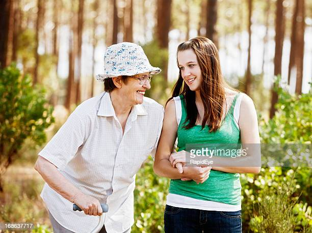 youth and age keep company: happy granny walking with granddaughter - osteoporosis stock photos and pictures