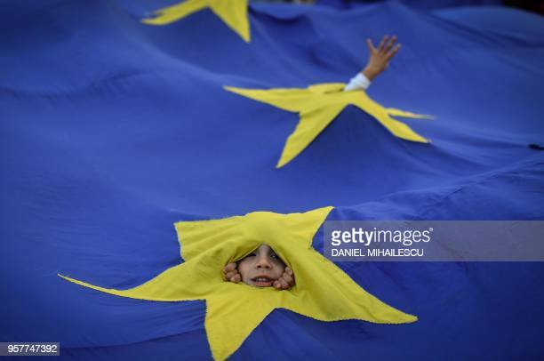 TOPSHOT A youth appears through an European flag during a protest asking for the resignation of the Romanian Prime minister on May 12 2018 in front...