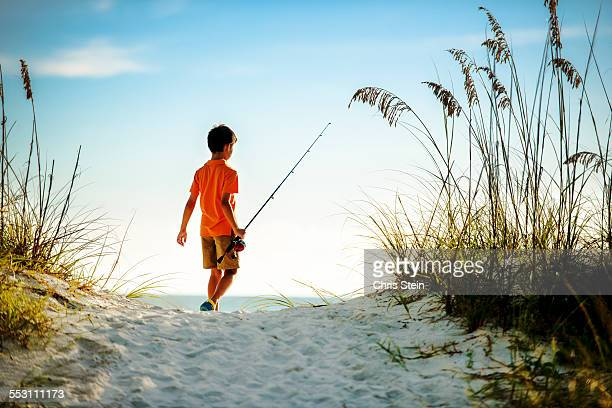 Youth Asian boy fishing at the beach at sunset.