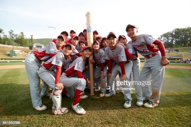 Little League World Series Japan Region team victorious posing with a giant autographed bat souvenir after defeating USA Southwest Region during...