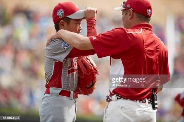 Little League World Series Japan Region Tsubasa Tomii talking to manager Junnji Hidaka vs USA Southwest Region during Championship Game at Howard J...