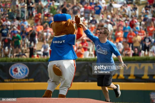 Little League World Series Little League Hall of Excellence member Champ Pederson giving high five to mascot Dugout before Championship Game between...