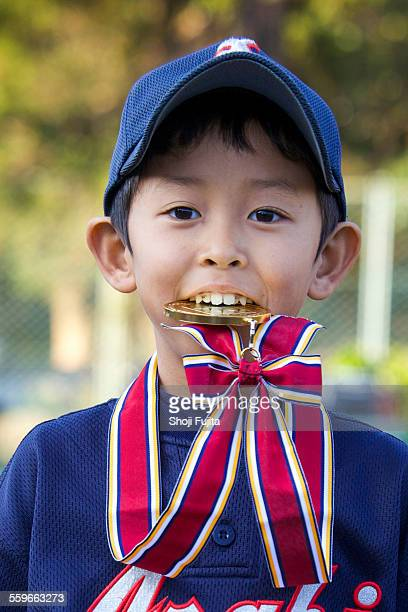 youth baseball player biting gold medal - 噛む ストックフォトと画像