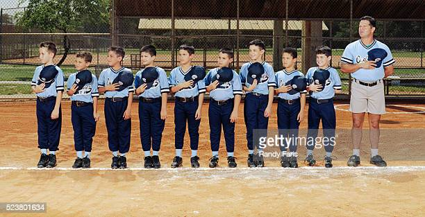 youth baseball team holding caps over hearts - baseball team stock pictures, royalty-free photos & images