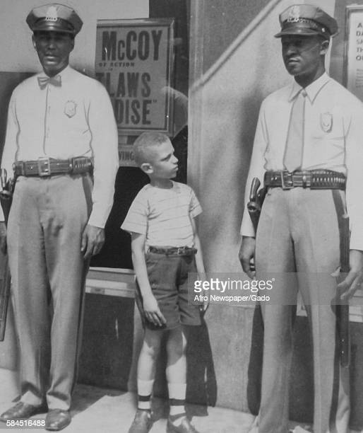 Youth Charles McGlotten looks at two African-American police officers in uniform and says that he wants to be a police officer when he grows up,...