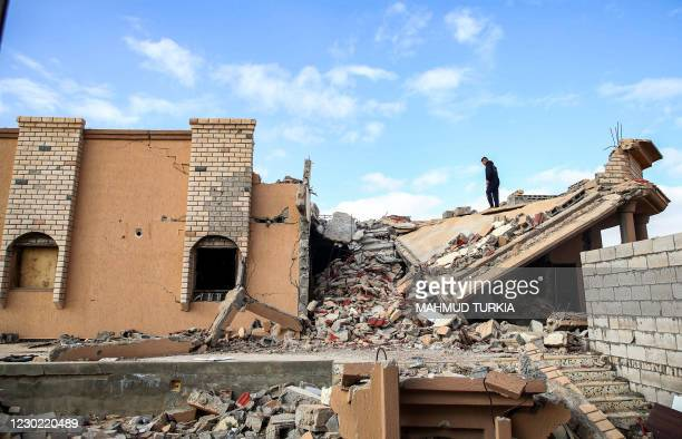 Youth climbs the rubble of a destroyed building in the city of Tawergha, some 200 kilometres east of Libya's capital close to the port city of...