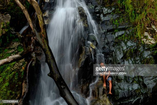 Youth cools off at a waterfall in Samadua of Aceh Province on July 9, 2020.