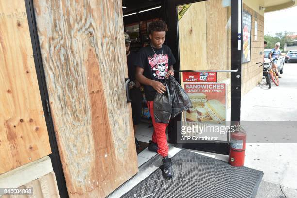 A youth departs a boarded convenience store as Hurricane Irma approaches September 9 2017 in Port Charlotte Florida Hurricane Irma weakened slightly...