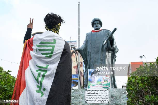 Youth draped in an Iraqi national flag flashes the victory gesture while standing before a statue of 19th century Iraqi cleric and poet Mohamed Said...