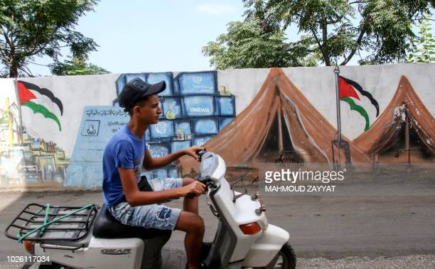 A youth drives a scooter past a mural depicting Palestinian refugee tents and a mock identity card for the Palestinian Ministry for Refugee Affairs...
