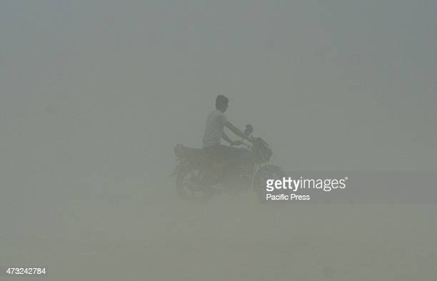 A youth drives motorcycle trough dust storm at Sangam the confluence of River Ganga Yamuna and Mythological Sarswati