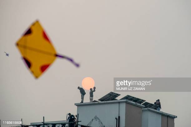 A youth flies a kite as others stand on the roofs of houses during the Shakrain festival or the Kite festival in Dhaka on January 14 2020 Shakrain...