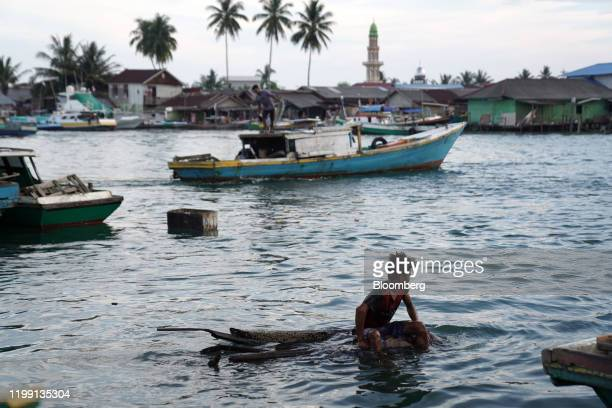 Youth floats on piece of wood off Manggar Village Pier in the port city of Balikpapan in East Kalimantan, Borneo, Indonesia, on Tuesday, Nov. 26,...