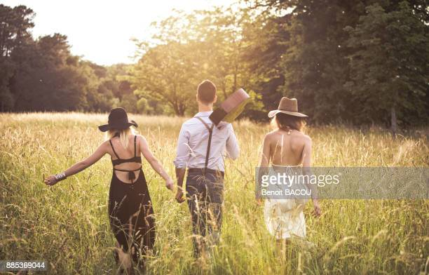 youth group hipster, back, ride in a field - white hat fashion item stock photos and pictures