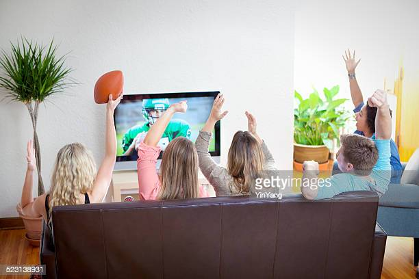 youth group watching sport football program on tv together - family watching tv stock pictures, royalty-free photos & images