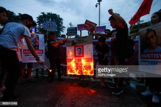 Youth groups burn a Duterte report card during the protest Youth groups protest against the alleged human rights violation of the current...